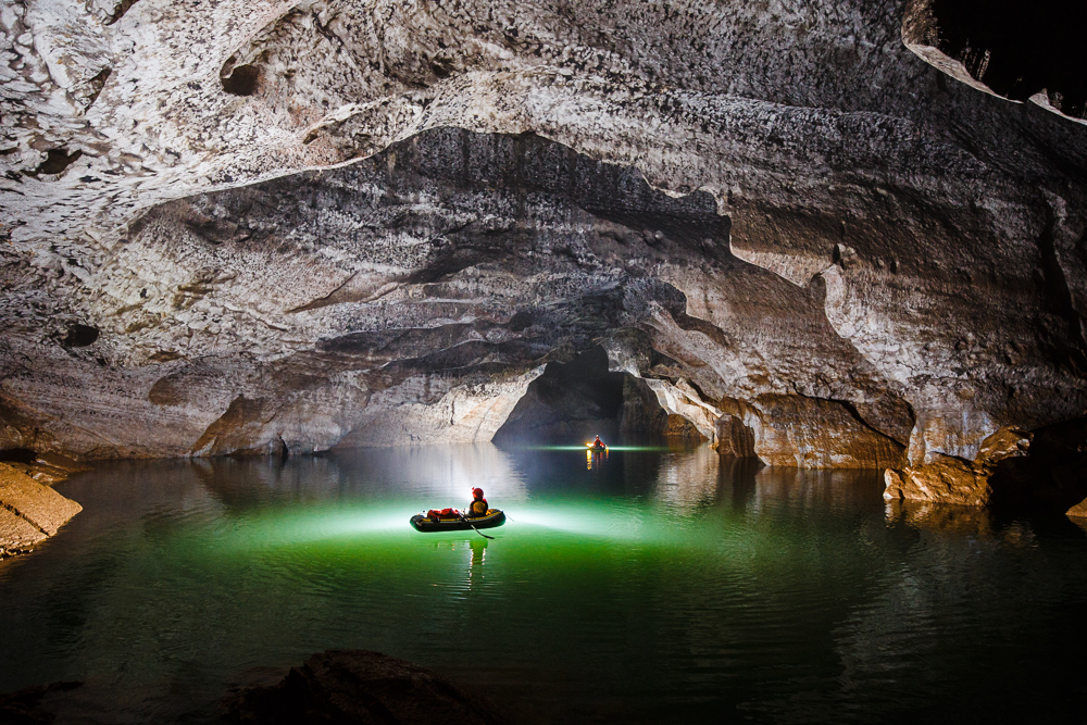 Cavers paddle boats in a cave near Daguan, China